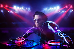 Disc jockey playing music with light beam effects on stage Royalty Free Stock Photos