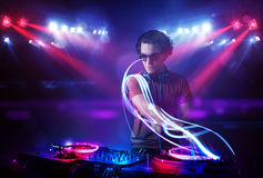 Disc jockey playing music with light beam effects on stage Stock Images