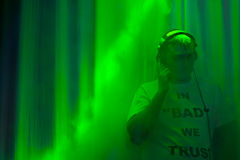 Disc jockey surrounded by green light from a spot. Disc jockey wearing headphones standing in a nightclub or disco surrounded by smokey green light from a spot stock image