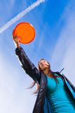 Disc and open sky. Woman holds a orange disc and attend to throw, blue sky on background Stock Photo