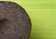 Disc of puer tea on green background Stock Images
