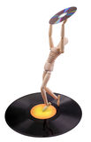 Disc technology evolution. Technology concept: wooden mannequin on vinyl disc holding compact disc Stock Photo