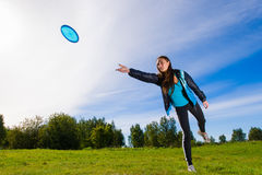 Disc and woman. Woman throws a blue disc on the lawn Royalty Free Stock Photos