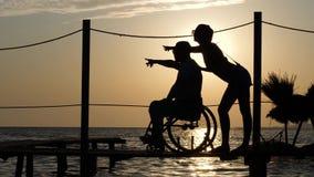 Discapacitado afortunado con mirada de la novia en distancia y demostraciones sus brazos al horizonte en puesta del sol del fondo almacen de video