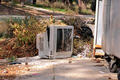 Discard TV sets on street, television near container thrown. Discard old TV sets on a street, television near the garbage container thrown, natural environment Stock Photo