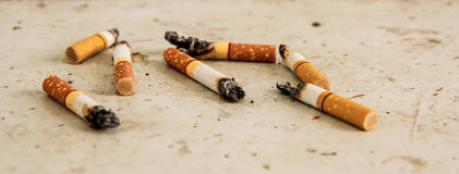 Discarded cigarette butts scattered Royalty Free Stock Image