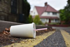 Discarded drinks container lying at the edge of an urban street. A carelessly discarded drink or soda container with drinking straw lies in the gutter of an royalty free stock photo