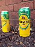 Discarded empty Holsten Pils Beer Cans by a brick wall stock image