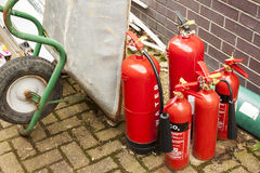 Discarded fire extinguishers in a builders yard. Old discarded fire extinguishers in a builders yard with a wheel barrow and a pile of rubbish Stock Photography