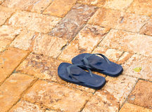 Discarded flipflops on paved deck by pool Royalty Free Stock Photos