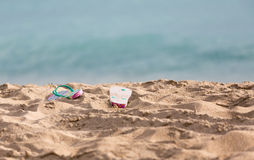 Discarded flipflops on sandy beach by ocean Stock Image