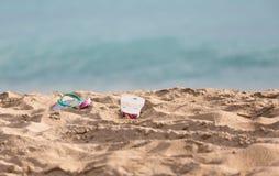 Discarded flipflops on sandy beach by ocean Stock Image