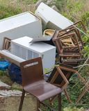 A discarded fridge and chairs. A discarded fridge, cupboard, binbags  and chairs litter the uncut grass of back garden royalty free stock image