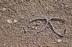Discarded metal glasses frame. Abstract view of discarded metal glasses frame on the ground Royalty Free Stock Photography
