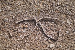 Discarded metal glasses frame. Abstract view of discarded metal glasses frame on the ground Stock Image