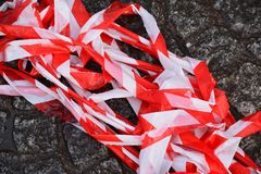 Red and white barrier tape in a pile on the ground Royalty Free Stock Photo