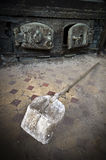 Discarded rusty shovel. Rusty shovel in front of old oven Stock Photography