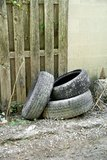 Discarded Tires. Some old tires discarded behind a residential garage in a city Royalty Free Stock Photo