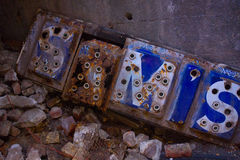 Vintage Electric Sign. Abandoned blue and white lettered sign in refuse pile of old bricks Royalty Free Stock Photography