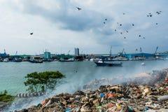 Discarica vicino alla vista del porto in pieno di fumo, della lettiera, delle bottiglie di plastica, dei rifiuti e dei rifiuti al Fotografia Stock