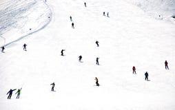Discesa totale degli sciatori della montagna dal pendio di collina Fotografia Stock