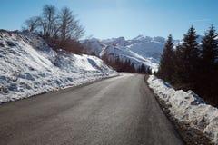 Discesa vuota sulle alpi, cielo blu della strada della montagna Immagine Stock