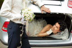 Discharge of captive bride. Groom discharging of captive bride from car trunk royalty free stock image