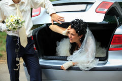 Discharge of captive bride. Groom discharging of captive bride from car trunk royalty free stock photo