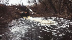 Discharge of sewage into a river. Dirty sewage from the pipe, environmental pollution.