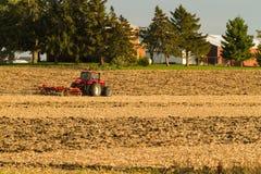 discing他的在一个凉快的10月下午的农夫领域 免版税图库摄影