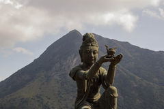 Disciple of Big Buddha. Bronze statue of disciple offering a gift to Big Buddha Stock Photo