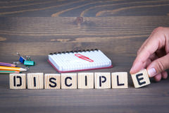 Disciple from wooden letters on wooden background. Disciple from wooden letters on dark texture background Stock Photo
