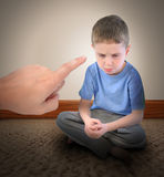 Discipline Boy Getting Time Out. A sad little boy is getting a time out with a finger pointing at the child for a discipline parenting concept Royalty Free Stock Images