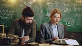 Discipline concept. Man with beard hold pen and sexy girl teacher prints on a typewriter , chalkboard on background. Lady teacher and strict schoolmaster care stock video