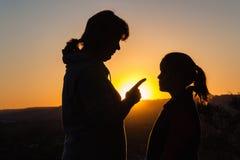 Discipline de fille de mère silhouettée Photos stock