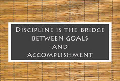 Discipline Poster. The following quote over a bamboo shade background Discipline is the bridge between goals and accomplishment stock photography