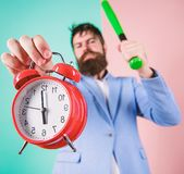 Discipline and sanctions. Boss aggressive face hold alarm clock. Destroy or turn off. Man suit hold clock and baseball. Bat in hands. Business discipline stock image