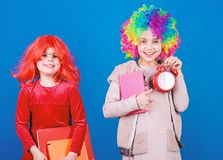 Discipline and time concept. Circus school education. Time to have fun. Kids colorful curly wig clown style hold alarm royalty free stock photo