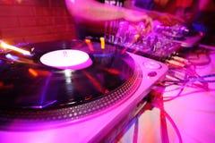 discjockey bak däcken i en nattklubb Royaltyfri Bild