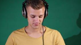 discjockey som dansar i hörlurar på den gröna bakgrunden arkivfilmer