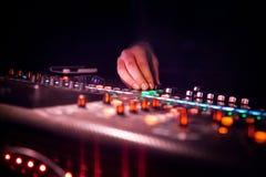 discjockey som fungerar soundboard eller blandar konsolbruk i solid inspelning och reproduktion royaltyfri bild