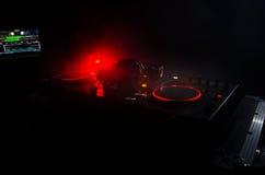 discjockey som rotera, blandar och skrapar i en nattklubb, händer av styrning för spår för dj-nyp olik på djs däck, strobeljus oc Arkivbilder
