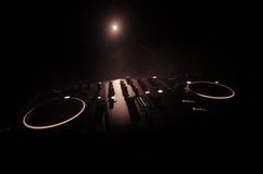discjockey som rotera, blandar och skrapar i en nattklubb, händer av styrning för spår för dj-nyp olik på djs däck, strobeljus oc Arkivbild