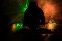 discjockey som rotera, blandar och skrapar i en nattklubb, händer av styrning för spår för dj-nyp olik på dj \ 's-däck, strobelju Arkivfoto