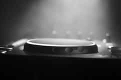 discjockey som rotera, blandar och skrapar i en nattklubb, händer av styrning för spår för dj-nyp olik på djs däck, strobeljus oc Arkivfoto