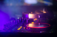 discjockey som rotera, blandar och skrapar i en nattklubb, händer av styrning för spår för dj-nyp olik på djs däck, strobeljus oc Royaltyfri Foto