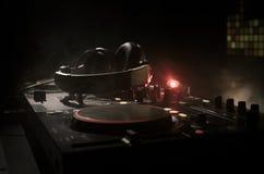 discjockey som rotera, blandar och skrapar i en nattklubb, händer av styrning för spår för dj-nyp olik på djs däck, strobeljus oc Royaltyfri Bild