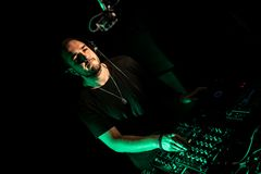 discjockey som spelar hus- och technomusik i en nattklubb Blanda och kontrollera musiken arkivbilder