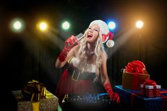 discjockeyflickan i den santa hatten sjunger in i mikrofonen på juldag Royaltyfri Foto