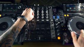 discjockeyhänder som blandar på en elektronisk nattklubb, festar stock video